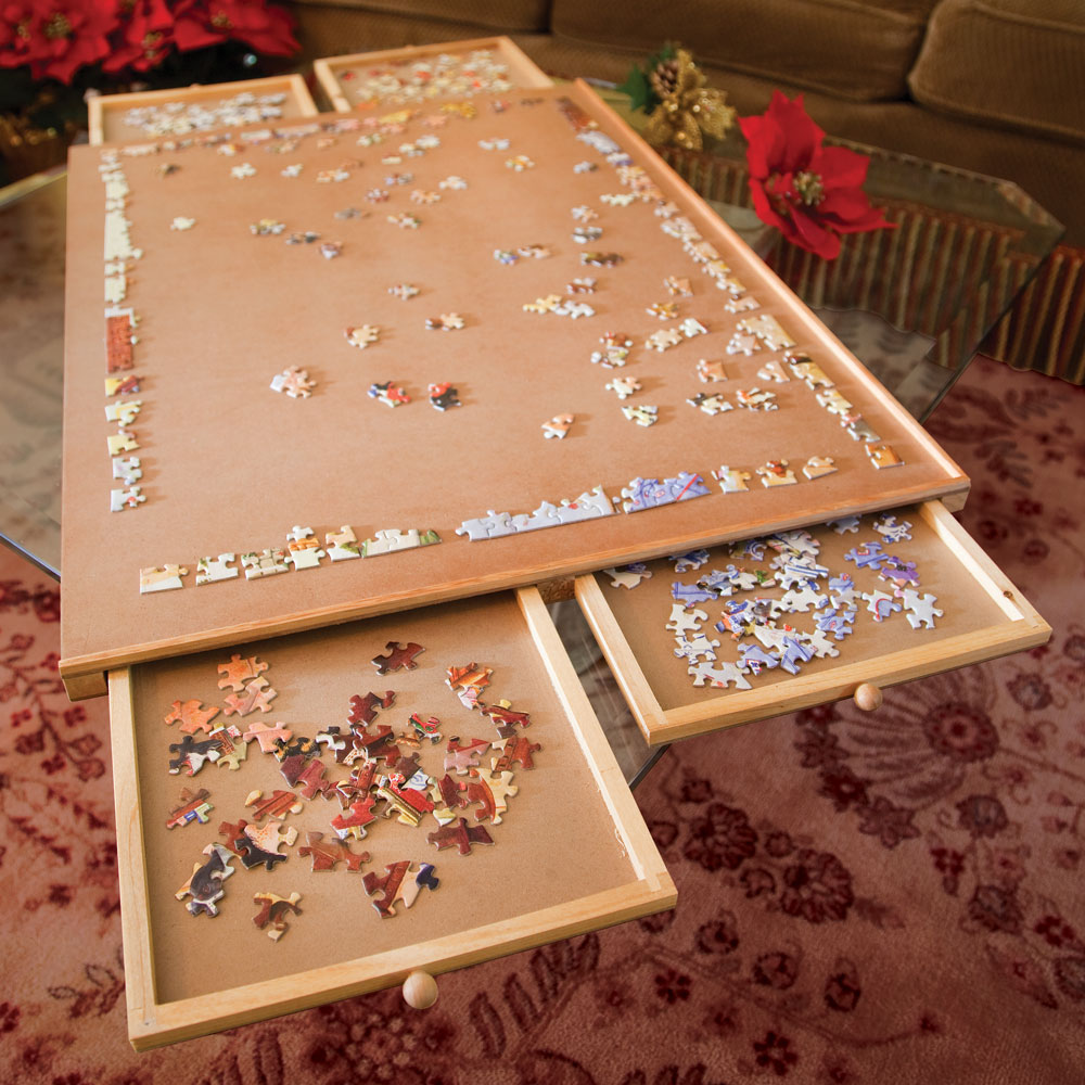 A photo of a wooden puzzle tray on a glass table. On the top of the tray, the borders of a large puzzle have been mostly assembled, with scattered pieces in the middle. The tray also has four shallow drawers (two on the left, two on the right) where other pieces look like they've been sorted by color - pieces with a lot of red and black are in one, and pieces with a lot of blue and white are in another.